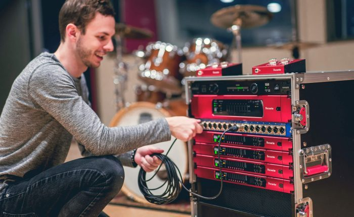 Luke Matyas, a student at the Music Technology program at Capital University, interacts with a gear setup including RedNet components from Focusrite